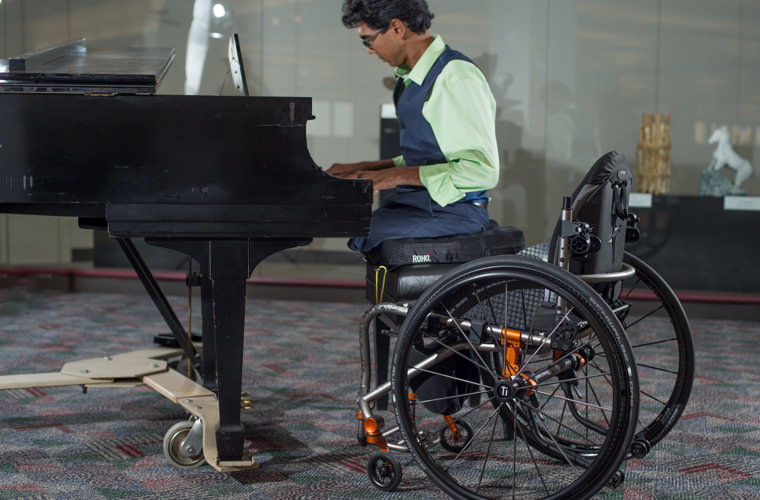 A man on a wheelchair playing piano.