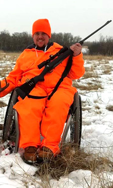 The man wearing orange over all jacket with gun on the Wheelchair