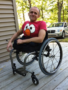 A disabled man wearing a bright smile on his Wheelchair