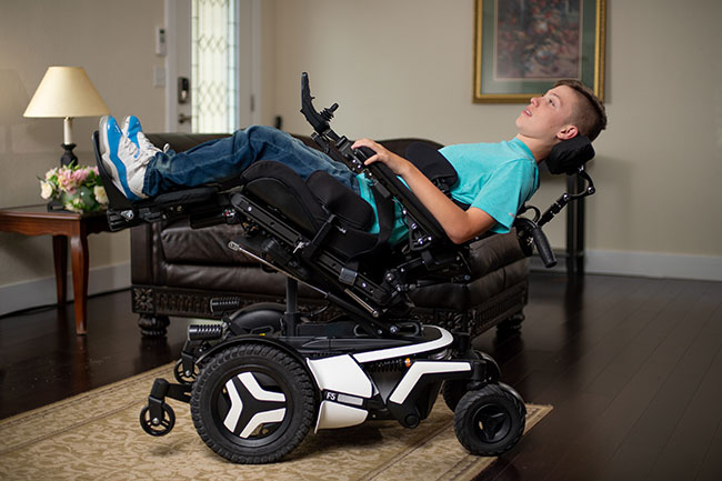 A man lying on the Tilt Permobil Power Wheelchair.