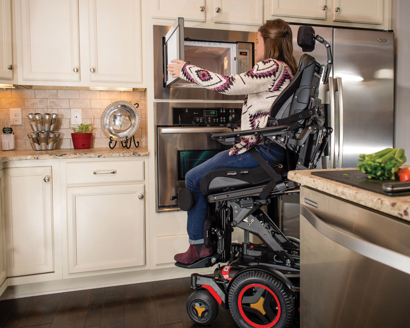 A Lady open her microwave on her power seating Wheelchair.