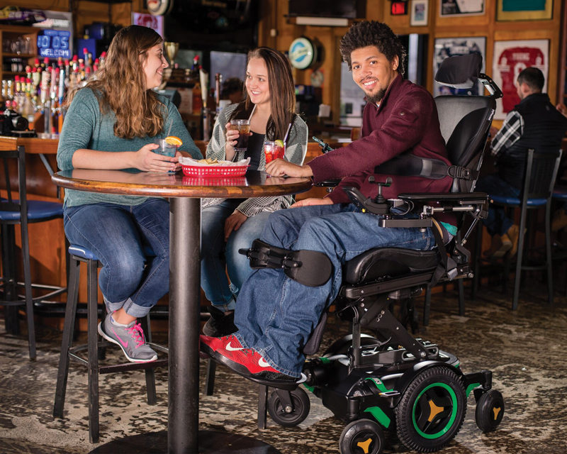 A man sitting on her wheelchair together his girl friends on the restaurant.