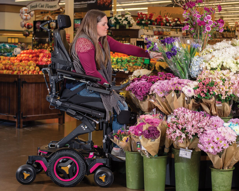 A girl pick a flower using her seating power wheelchair