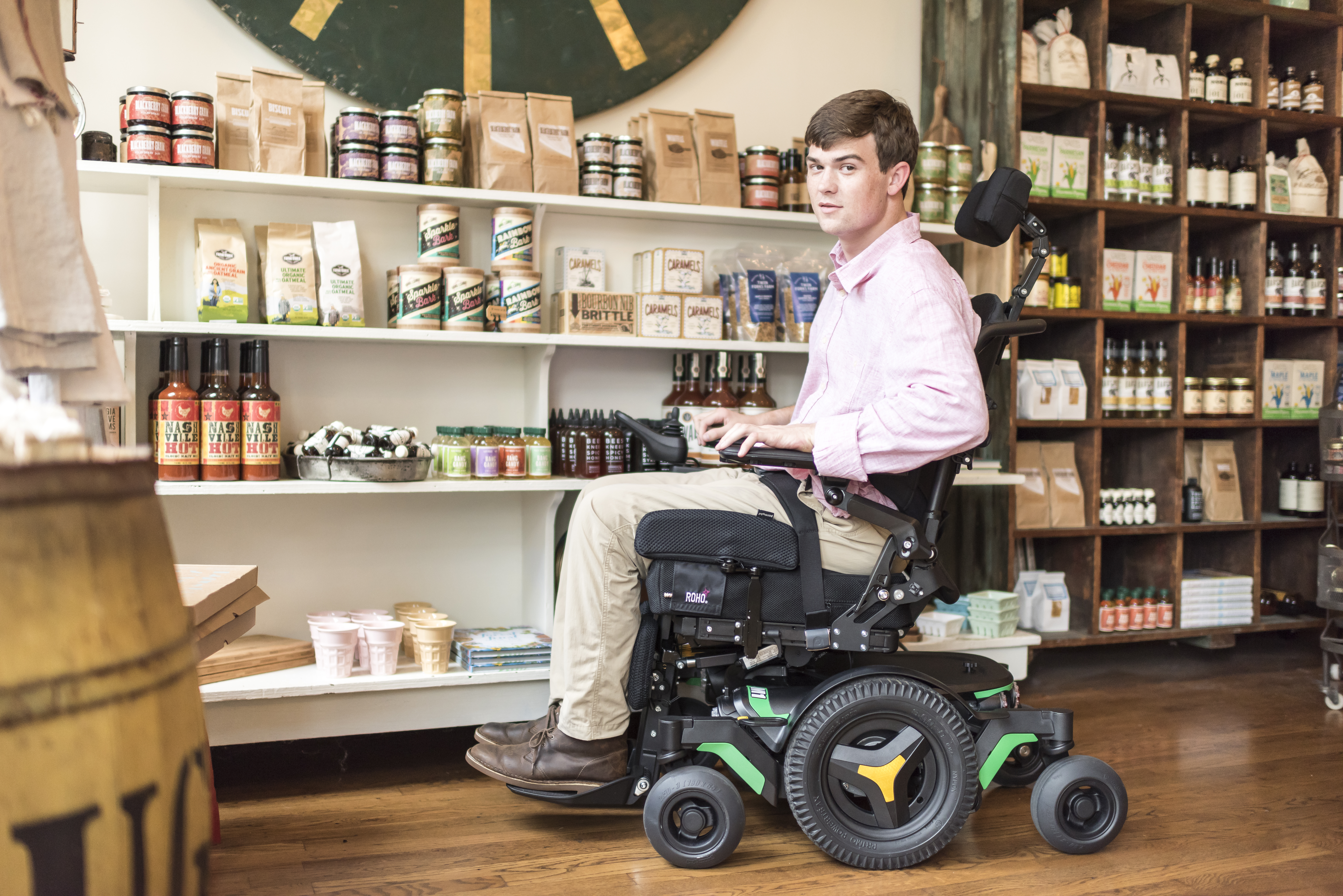 A man sitting on his power wheelchair at store.