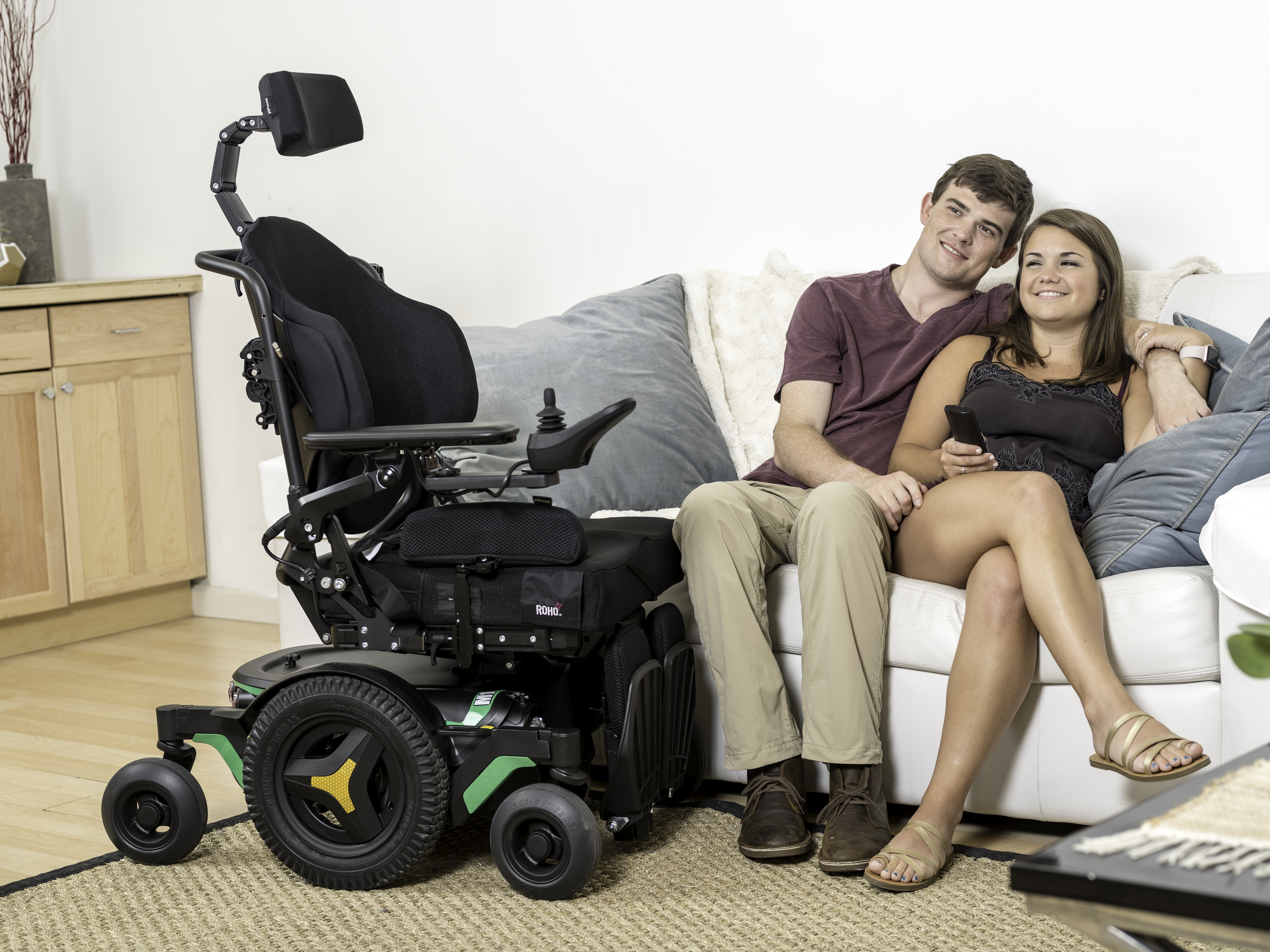 A couple sitting on sofa beside the power wheelchair.