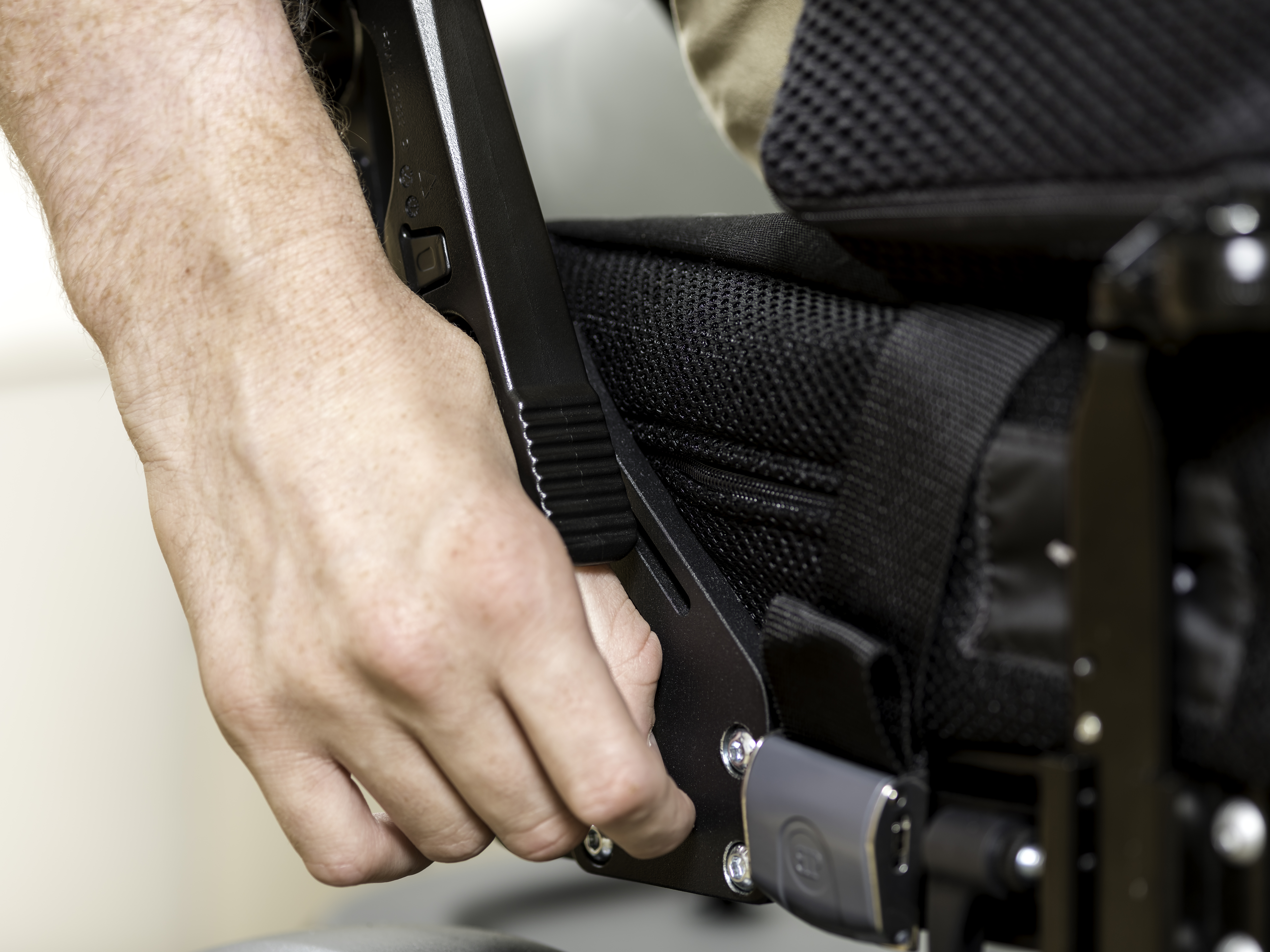A Hand on Seat Back Release Lever.