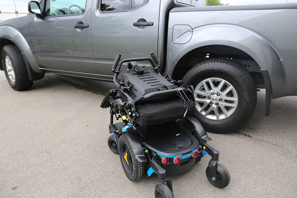 A Foldable Power Wheelchair beside the car.