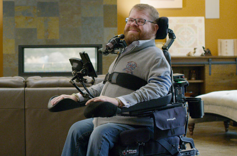 A man sitting on his wheelchair with proper position.