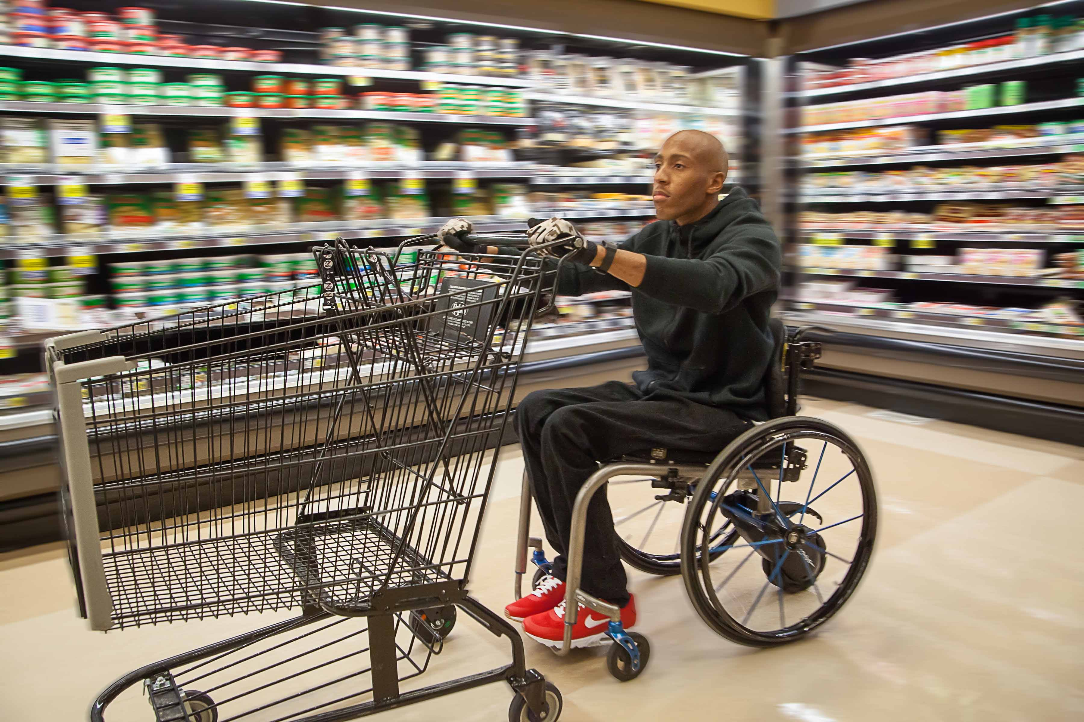 A disabled man on his smart drive wheelchair push a cart at the department store.