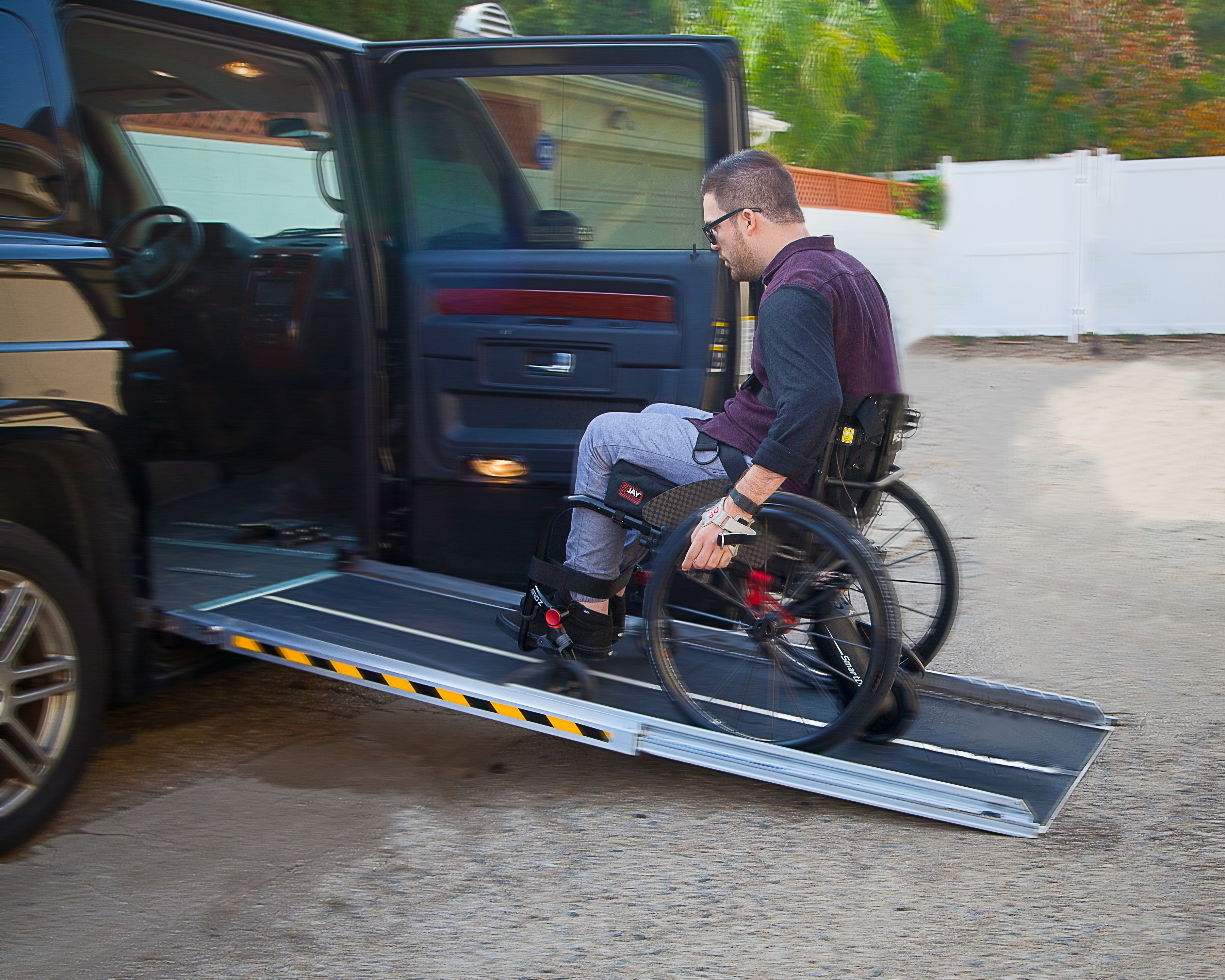 A disabled man rides his smart drive wheelchair to get into the car.
