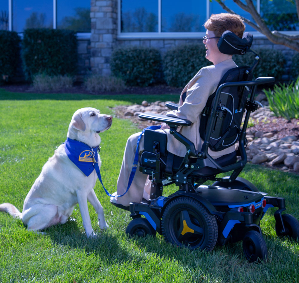A woman sat in a wheelchair with a dog