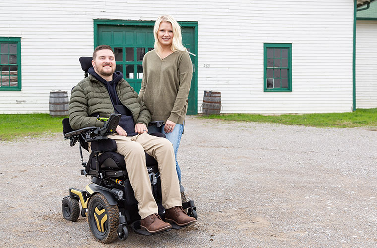 A boy sitting on a smartdrive wheelchair and a girl standing beside him